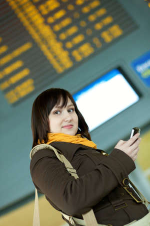 brune: Beautiful young girl sending sms in airport