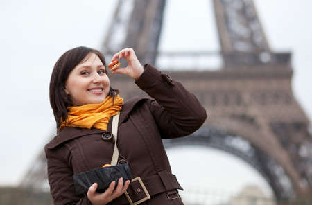 brune: Happy young girl eating macaroons in Paris