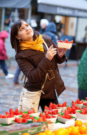 brune: Beautiful girl selecting strawberries at market