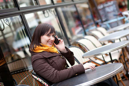 Happy young girl takling on cell phone in Parisian street cafe photo