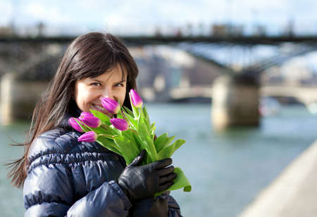 Happy beautiful girl with tulips enjoying spring day in Paris photo