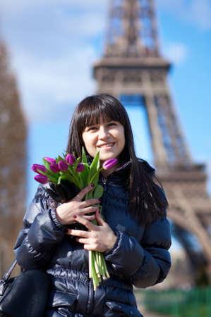 brune: Happy beautiful girl with tulips enjoying spring day in Paris