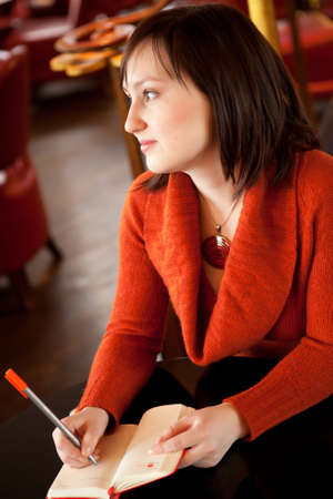 brune: Beautiful young woman writing something in her personal organizer in cafe