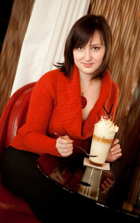 Beautiful young woman with delicious coffee cocktail in cafe Stock Photo - 12426039