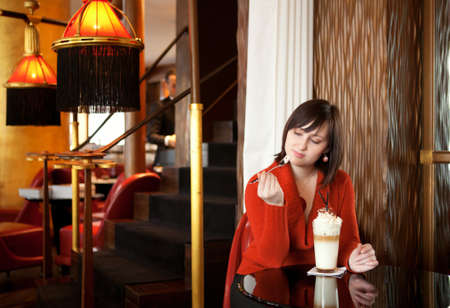 Beautiful young woman with delicious latte in cafe Stock Photo - 12426037