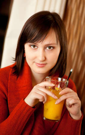 Beautiful young woman with orange juice in a cafe Stock Photo - 12426032