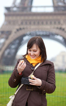 brune: Happy young woman eating macaroons near the Eiffel Tower Stock Photo