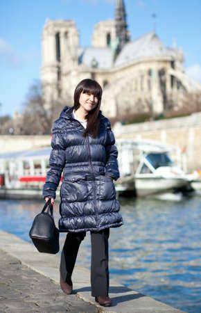 Beautiful brunette tourist walking at the emankment in Paris photo
