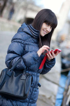 brune: Happy beautiful brunette tourist in Paris sending an sms to someone