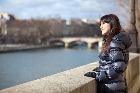 brune: Happy brunette girl at Parisian embankment enjoying warm spring day