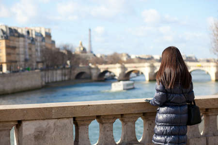 paris street: Alone brunette female tourist in Paris, looking at the Seine