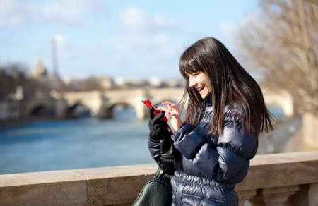 Happy beautiful brunette tourist in Paris sending an sms Reklamní fotografie - 12660073