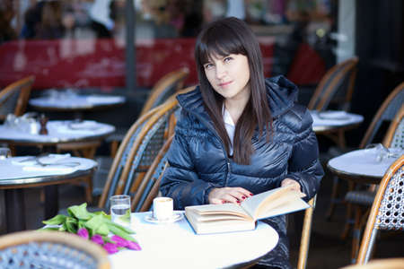 Dark-haired beautiful woman with book in Parisian street cafe photo