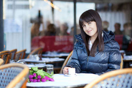 Smiling brunette lady in Parisian street cafe photo