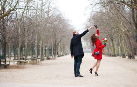 Happy couple dancing in the Luxembourg garden of Paris photo