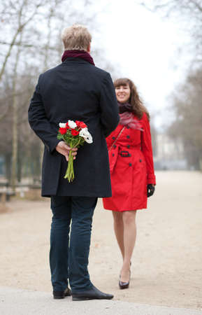 Happy couple having a date, man is going to offer flowers to his girlfriend Stock Photo - 12660207