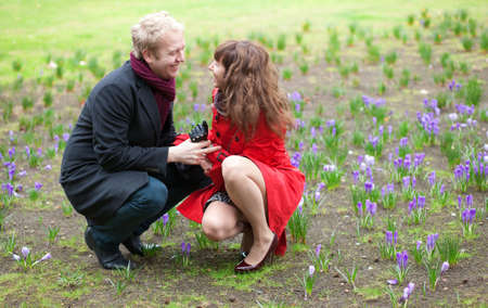 Romantic couple on their hunkers near fresh crocus at spring Stock Photo - 12827383