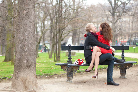 Happy romantic couple hugging on a bench photo