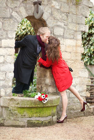 Dating couple kissing near the beautiful wall photo