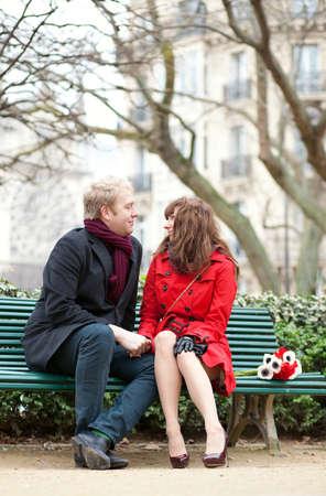 Dating couple sitting on a bench in Paris near the Notre Dame de Paris photo
