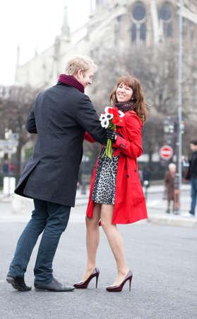 Happy couple dancing near Notre Dame de Paris photo