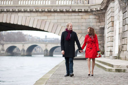 Beautiful romantic couple on a Parisian embankment at spring or winter photo