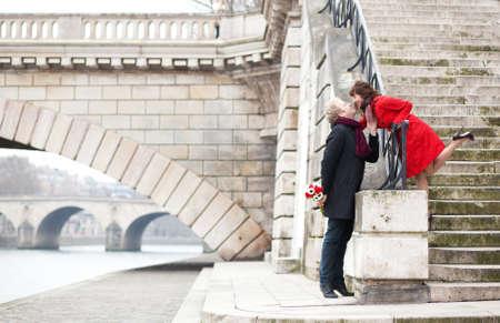 Beautiful romantic couple kissing on a Parisian embankment at spring or winter Reklamní fotografie