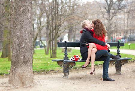 hombres besandose: Feliz pareja rom�ntica besos y abrazos en un banco Foto de archivo
