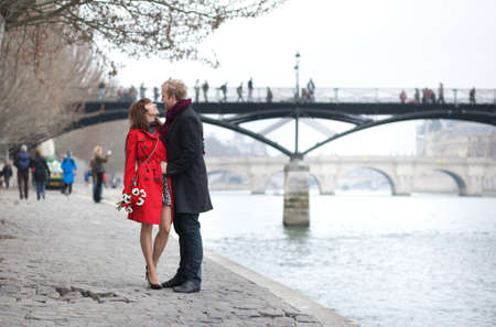 Romantic couple in love dating near Pont des Arts in Paris Stock Photo