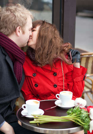 Happy couple kissing in Parisian cafe photo