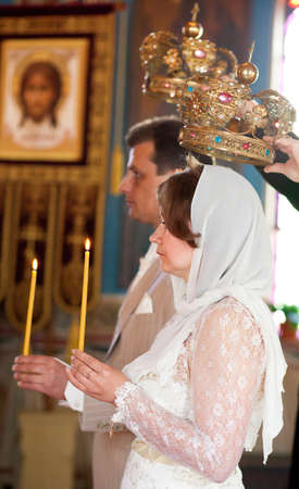 Bride and groom during orthodox wedding ceremony with candles and crowns photo