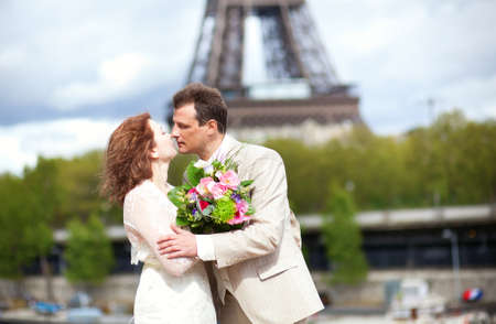 Just married couple is kissing near the Eiffel Tower photo