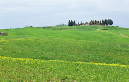 Typical Tuscany scenic landscape with a farmhouse on top of a hill photo