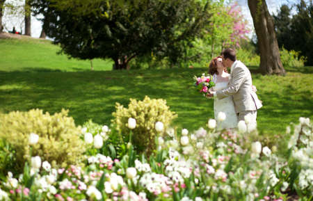 Happy just married couple kissing in park photo
