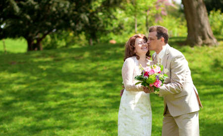 Happy just married couple kissing in park at sunny day photo