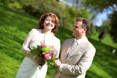 Happy just married couple in park at sunny day photo