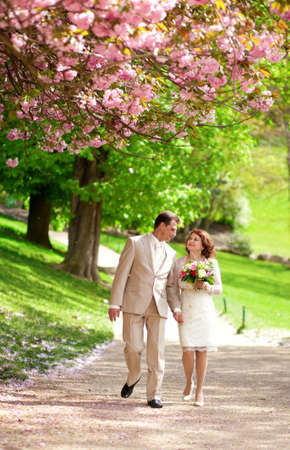 Beautiful newlywed couple having a stroll in park at spring photo
