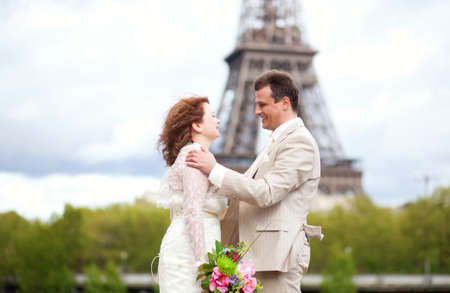 Wedding in Paris. Happy just married couple hugging near the Eiffel Tower photo