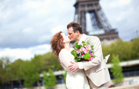 Wedding in Paris. Happy newlywed couple kissing near the Eiffel Tower photo