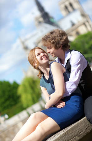 Young romantic couple enjoying warm sunny day in Paris, near the Notre-Dame  photo