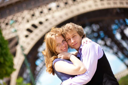 Vacation in Paris. Young romantic couple hugging under the Eiffel Tower Stock Photo - 13580316