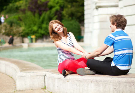 Young happy couple sitting near water and holding hands photo
