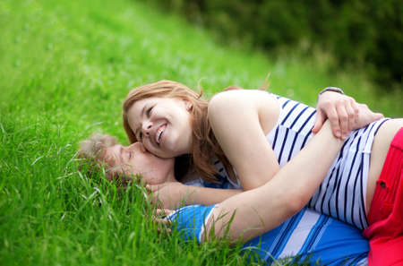 Romantic couple lying on the grass and hugging photo