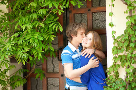 Young loving couple kissing by the door photo