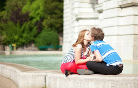 Romantic dating couple kissing by the fountain