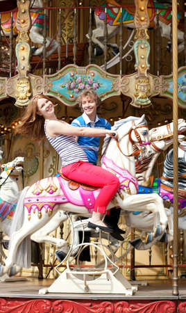 Cheerful young couple enjyong their ride on merry-go-round Stock Photo - 13792175
