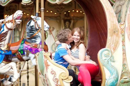 Happy young couple kissing in an equipage of vintage Parisian merry-go-round