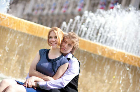 Young loving couple and beautiful fountain water jets photo