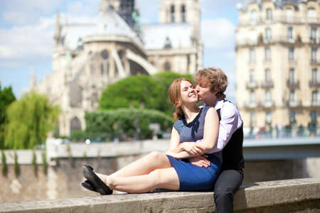 Romantic summer day in Paris, couple of tourists sitting by Notre Dame photo