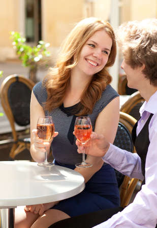 Beautiful couple having a date in a cafe and drinking rose wine photo